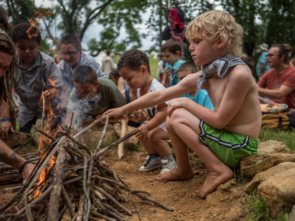 Young boys learning to start a fire
