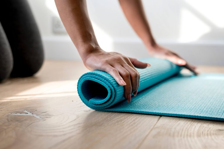 person holding yoga mat